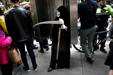 A climate activist in costume takes a break in a phone booth during Extinction Rebellion protests in lower Manhattan in New York