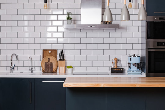 Kitchen with white tiles and dark furniture
