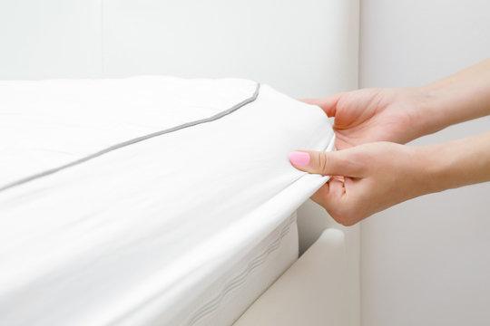 Woman's hands changing white mattress cover. Regular bed linen change. Closeup.