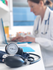 Health check, Doctor examining patients records after a consultation with the focus on a blood pressure gauge
