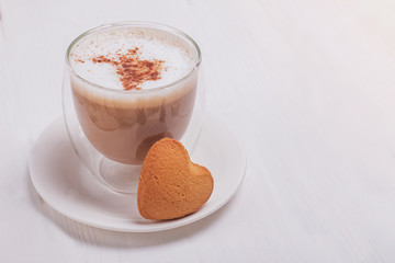 Fotobehang - Hot latte in a glass cuo topped with cinnamon and a small heart shaped bisquit