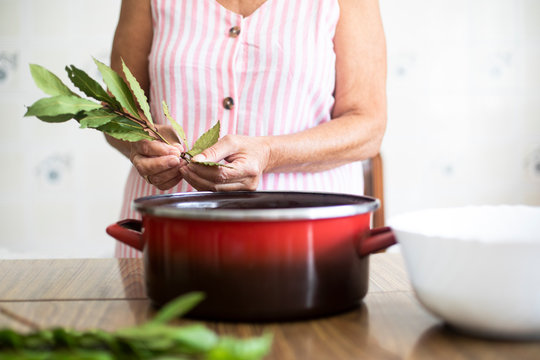 Woman using laurel for cooking in kitchen