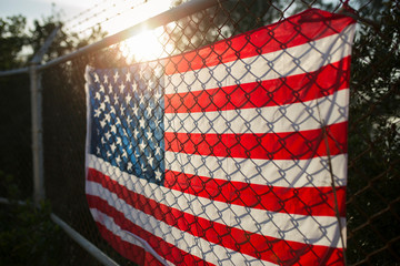 US-American flag on barbed wire fence, close up