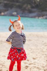 Portrait of girl standing on the beach wearing devil's horns