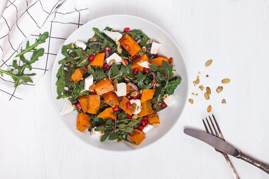 Delicious seasonal salad with pumkin or squash, arugula and feta cheese