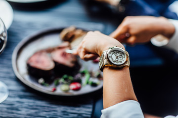 Beautiful young woman eating steak in restaurant,close up picture. Woman hands with watch.