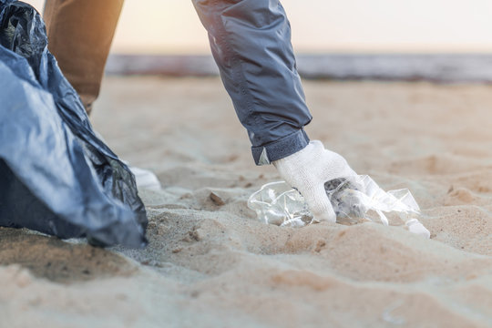 Close up of man's hand picking up trash and plastics cleaning the beach with a garbage bag