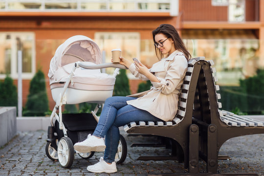 Successful mother with a newborn baby in a stroller drinks tea or coffee in a street, near home and holding phone. Fashionable modern mom with a baby. Relaxing near the park.