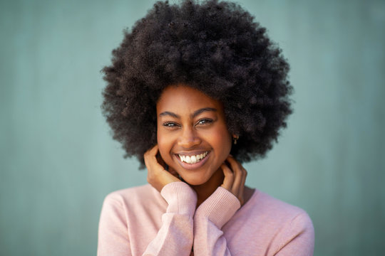 front portrait of attractive young african american woman with afro smiling and hand on face