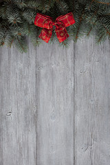 Christmas wooden background with spruce branches and red ribbon bow