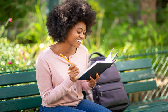 young smiling african american woman sitting outside writing in book