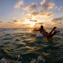 Woman on surfboard swimming in beach