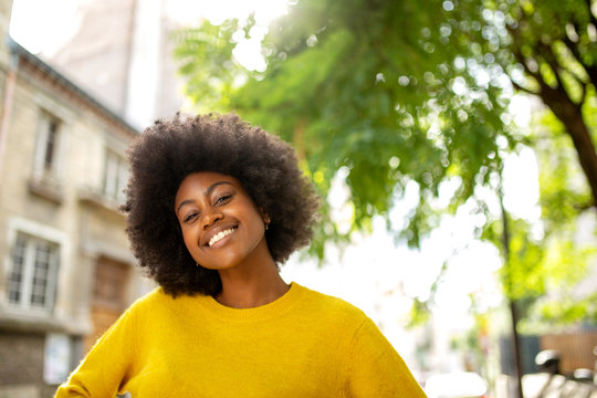 happy black girl with afro smiling outside in city
