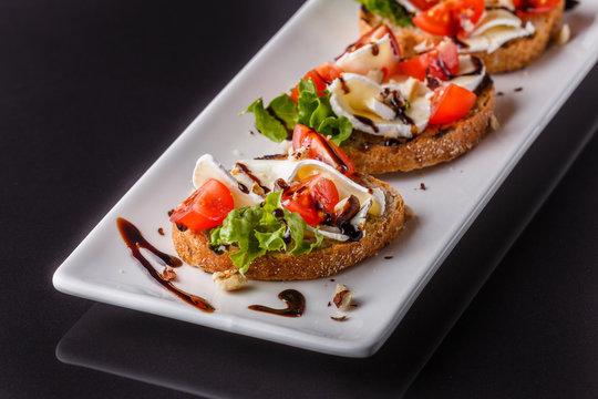 Bruschetta with tomatoes, lettuce, camambert, balsamic vinegar