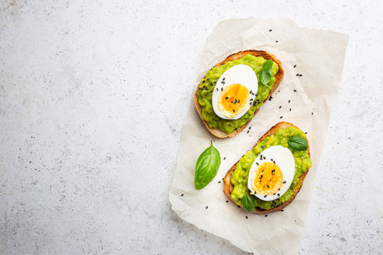 Healthy breakfast, toast with avocado and egg, top view, copy space. Vegetarian food concept