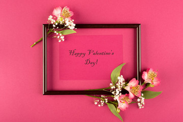 Valentine's day concept. Bouquet of alstroemeria and write Happy Valentine's Day on a red paper background. Top wive