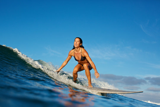 Woman surfing on sea wave