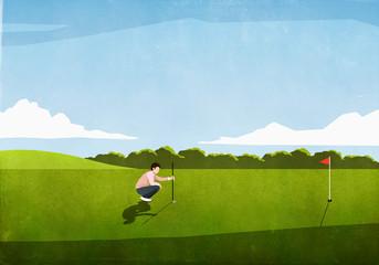 Male golfer preparing tee shot on sunny golf course