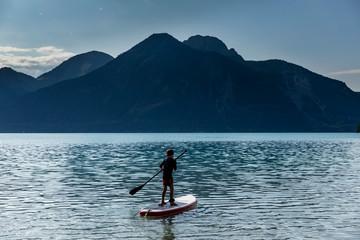 Boy paddleboarding on sunny, idyllic mountain lake, Walchensee, Bavaria, Germany