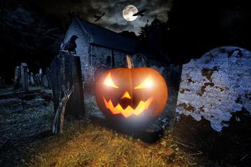 glowing orange halloween pumpkin with scyry zombie hand on old graveyard front of full moon black raven church dark night spooky horror background