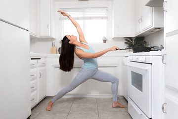 Fit female cooking and exercising at the same time, funny lifestyle advertisement, yoga pose in tiny home