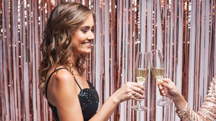 Portrait of two beautiful elegant women clinking champagne glasses.