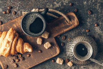 Fototapete - Coffee and croissant on dark textured background.