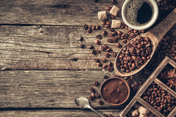 Wall Mural - Coffee cup with coffee beans on wood background.