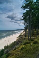 widok w słoneczny dzień na pustą plażę bałtycką w okolicach Ustki i gęsty sosnowy las na...