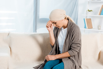 upset and sick woman with head scarf in living room