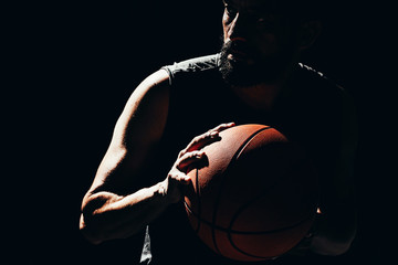 Dramatic portrait of basketball player over dark background