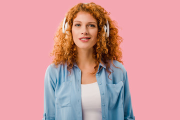 beautiful redhead woman listening music in headphones, Isolated On pink