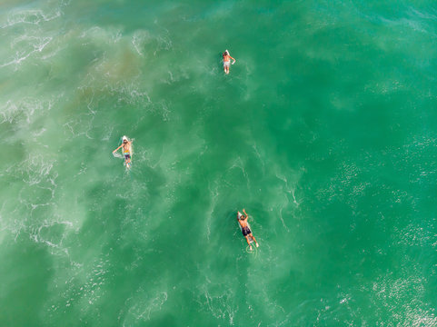 A view from above of the surfers in the ocean