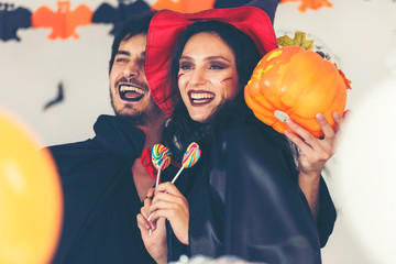 Party Halloween holiday.  Young couple party and celebrate with Halloween pumpkin and cocktails with having fun and happy at home. Wall mural