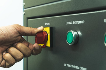 Close up of Worker hand twist main power switch before operating testing machine