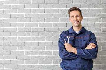Male car mechanic near brick wall