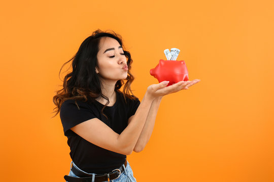 Happy Asian woman with piggy bank on color background