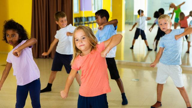 Portrait of smiling children practicing sport dance in modern dance hall
