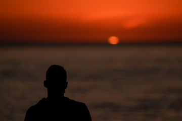 A man watches the sun set  as he looks out at the Pacific Ocean from Encinitas, California