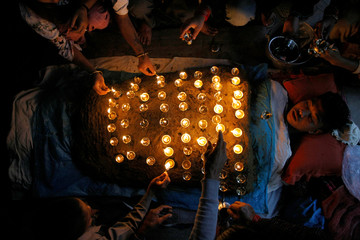 """A devotee lies covered with oil lamps placed by other devotees while offering prayers as part of a ritual during """"Dashain"""" in Bhaktapur"""
