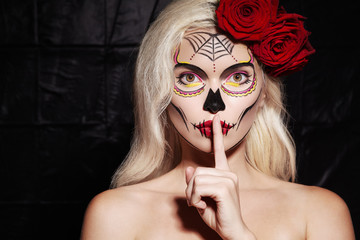 Halloween Make-Up Style. Blond Model Wear Sugar Skull Makeup with Red Roses. Santa Muerte Concept....