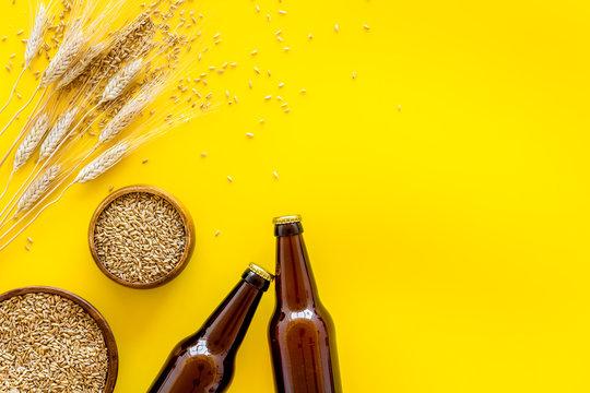 Beer ingredients. Barley near beer bottles on yellow background top view copy space