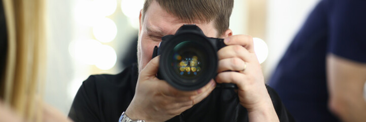 A male photographer holds camera in his hand concept. The self-portrait is reflected in the mirror.