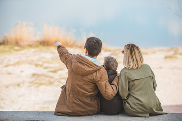 young beautiful family sitting at beach with view lake