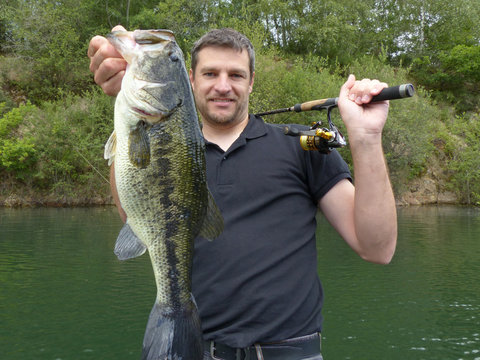 Lucky fisherman holding a large bass fish. Freshwater fishing, lure fishing