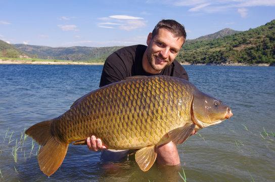 Carp fishing, man holding a big common carp. France