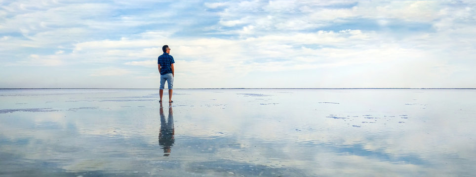 man in the water at sea. concept of a happy holiday and freedom. tourist looking at the horizon line. Beautiful panorama of the salt lake with the reflection of white clouds in the ode.