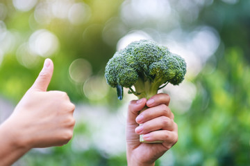 a woman holding and making thumb up to show good sign to a green broccoli