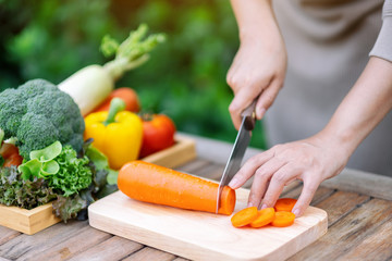Closeup image of a woman cutting and chopping carrot by knife on wooden board