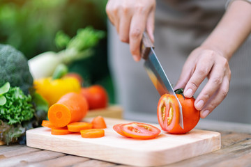Closeup image of a woman cutting and chopping tomato by knife on wooden board